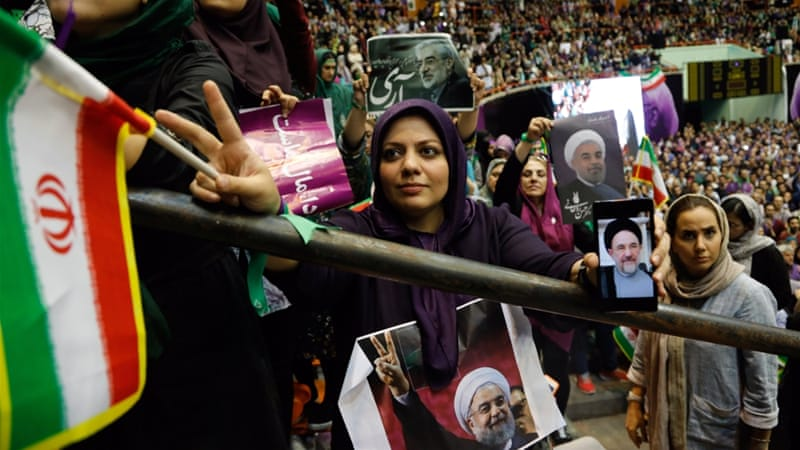 Supporters of Iran's President Hassan Rouhani listen to his speech as they hold his pictures during an election campaign rally in Tehran, Iran [Reuters]