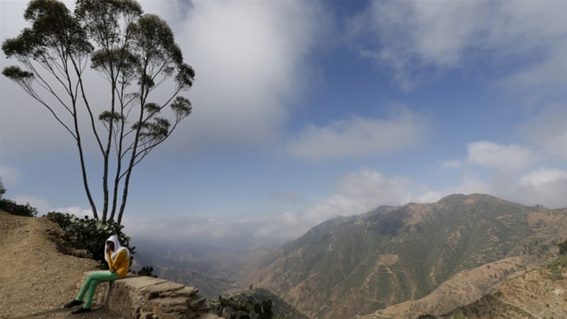 A woman sits next to an escarpment on the outskirts of Asmara, Eritrea [Thomas Mukoya/Reuters]