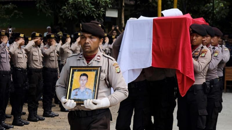 Indonesia policemen carry the coffin of one of their colleagues killed in Wednesday's attack [Reuters]