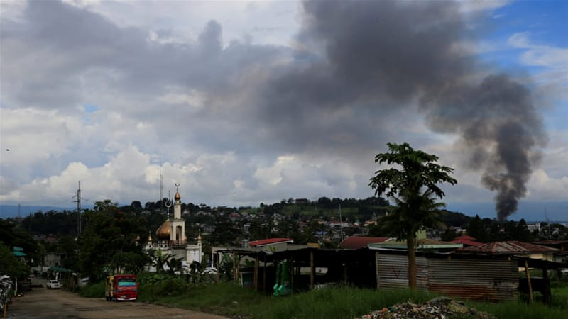 A black smoke comes from a burning building at a Marinaot town, after government troops clash with fighters from the Maute group [Romeo Ranoco/Reuters]