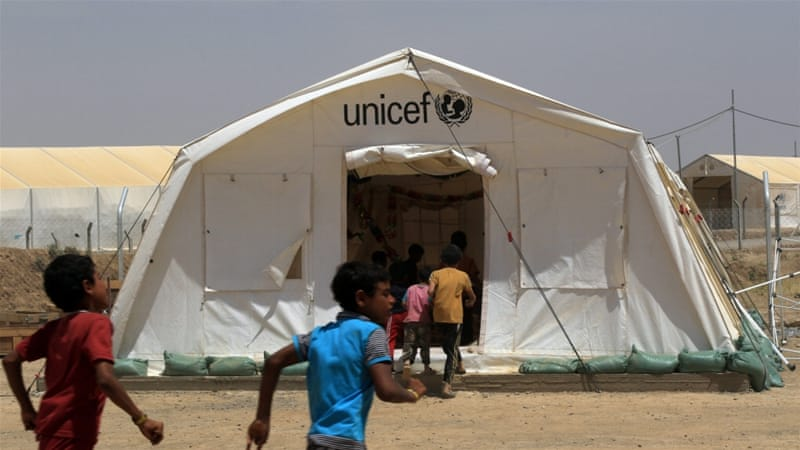 Displaced Iraqi boys enter a tent school set by United Nations Children's Fund (UNICEF) at Hammam al-Alil camp south of Mosul [Ari Jalal/Reuters]