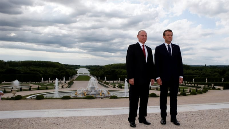 French President Emmanuel Macron and Russian President Vladimir Putin pose in the gardens of the Versailles Palace following their meeting [Francois Mori/Reuters]