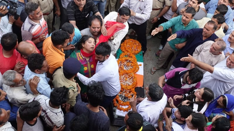 People gather to pay their respects next to a coffin containing the body a CRPF officer, who was killed in a Maoist ambush in India in April [Sanjay Baid/EPA]