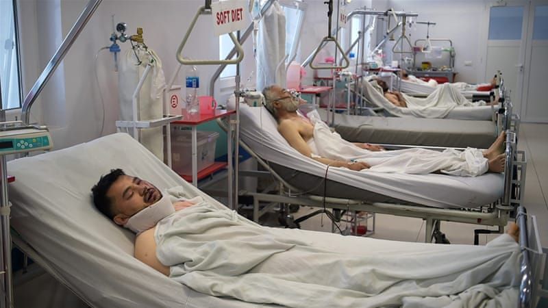 Wounded Afghan men receive treatment at a hospital in Kabul [Shah Marai/AFP]