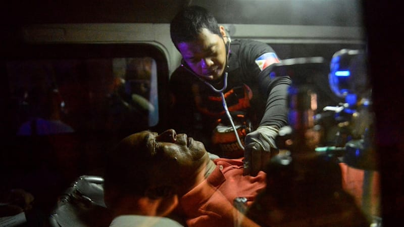 A rescue worker helps a victim in an ambulance outside the Resorts World Hotel in Manila [Ezra Acayan/AFP]