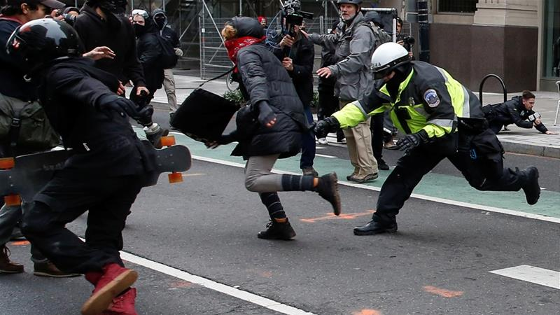 A police officer tries to tackle a protester demonstrating against US President Donald Trump on the sidelines of the inauguration [File: Adrees Latif/Reuters]