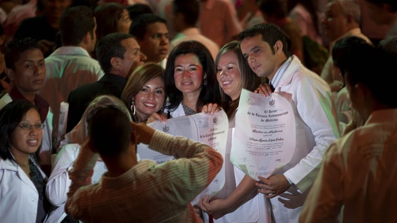 Just graduated doctors have their picture taken holding their diplomas after a graduation ceremony at the Karl Marx theatre in Havana, Cuba. [AP Photo/Ramon Espinosa]