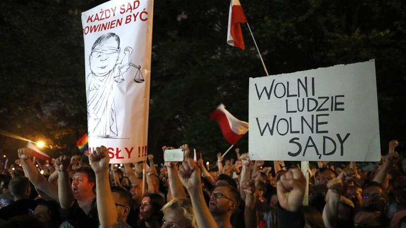 "People shout slogans during a protest against supreme court legislation outside the Parliament in Warsaw, Poland on July 21. The poster reads ""Free people, free courts"" [Reuters/Kacper Pempel]"