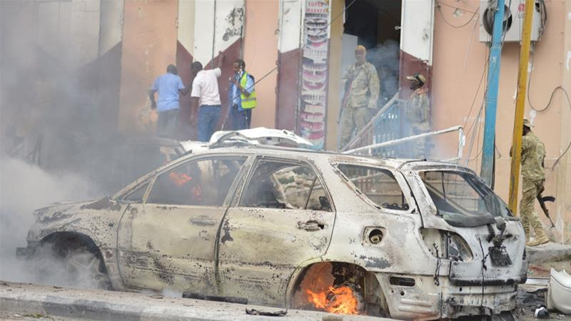 A car burns in the Somali capital after exploding in the city centre [Abdirisak Mohamud Tuuryare/Al Jazeera]