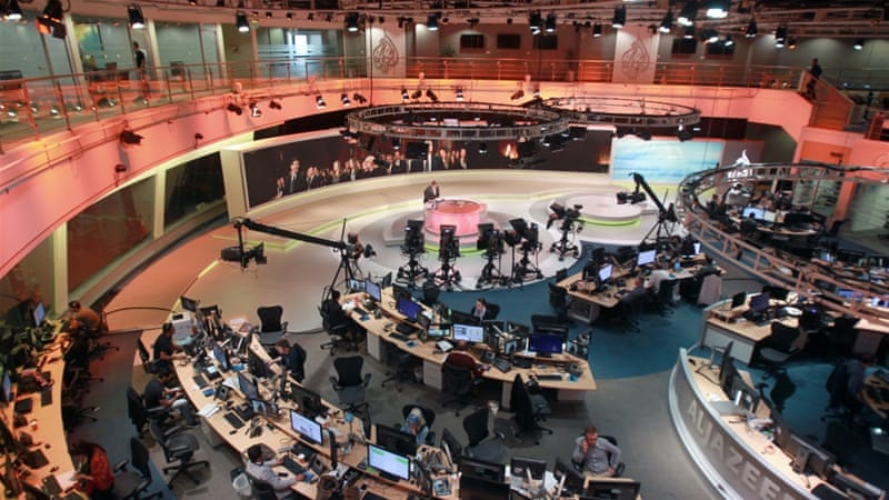 Staff work inside the headquarters of Al Jazeera Network, in Doha, Qatar [Naseem Zeitoon/Reuters]