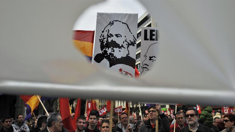 A face of Karl Marx is seen through a hole in a banner as people in Spain march to protest against the conservative government's tough labour reforms in 2012 [Alvaro Barrientos/AP]