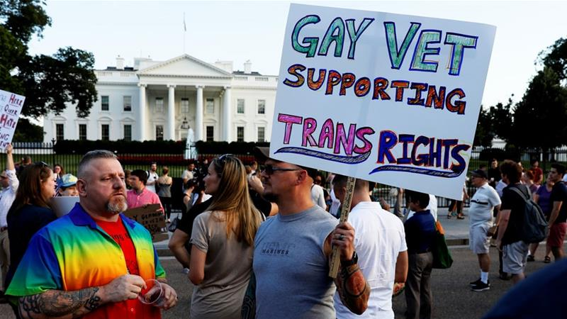 Demonstrators gather to protest Trump's announcement that he plans to reinstate a ban on transgender individuals from serving in any capacity in the US military [File: Jonathan Ernst/Reuters]