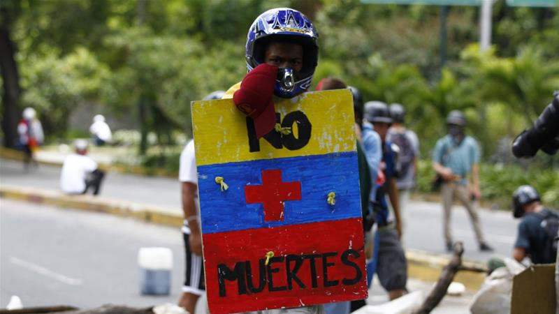 An opposition supporter holds a shield that reads 'No more deaths' as clashes break out in Caracas on July 30 [Reuters/Christian Veron]
