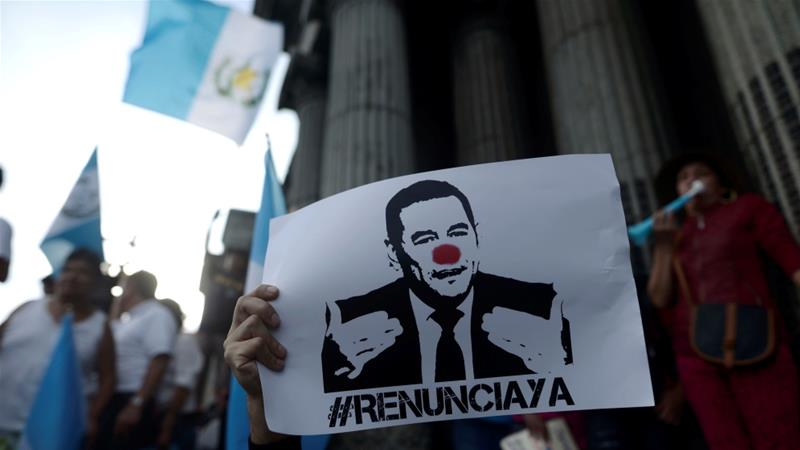 A demonstrator holds a sign calling for the resignation of Guatemalan President Jimmy Morales in Guatemala City on August 27 [Reuters/Fabricio Alonzo]