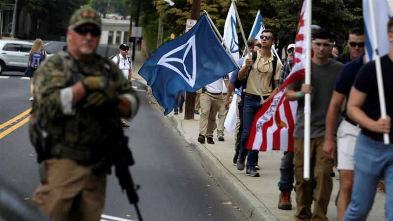 White nationalists, carrying the Identity Evropa flag, pass a militia member at a rally in Charlottesville [File: Joshua Roberts/Reuters]