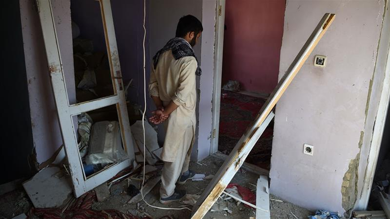 A Kabul resident walks through a damaged house following a NATO air strike