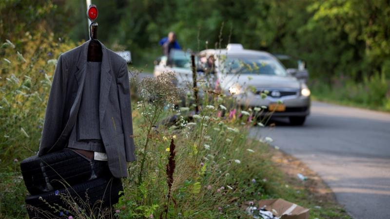 A man's suit hangs off a street marker as a cab carrying asylum seekers pulls up near the US-Canada border in Champlain, New York [Christinne Muschi/Reuters]