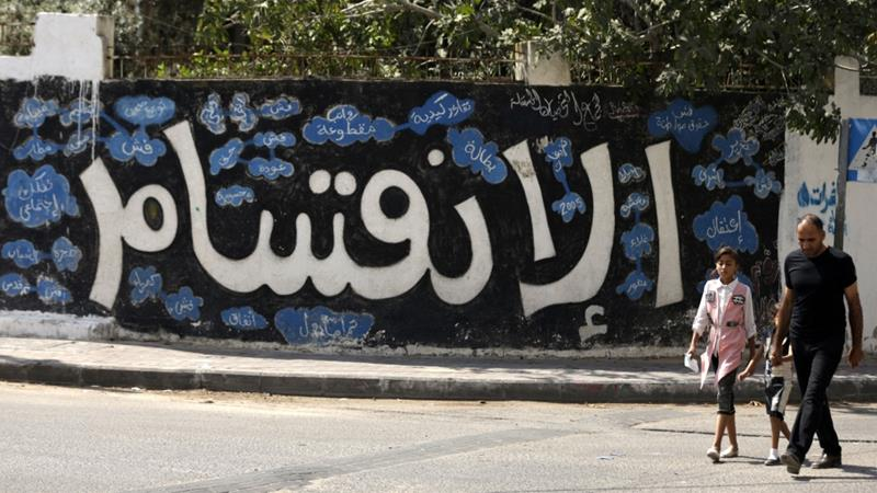 People Walk Past Graffiti Reading Division After Hamas Announced Steps Towards Resolving A Decade