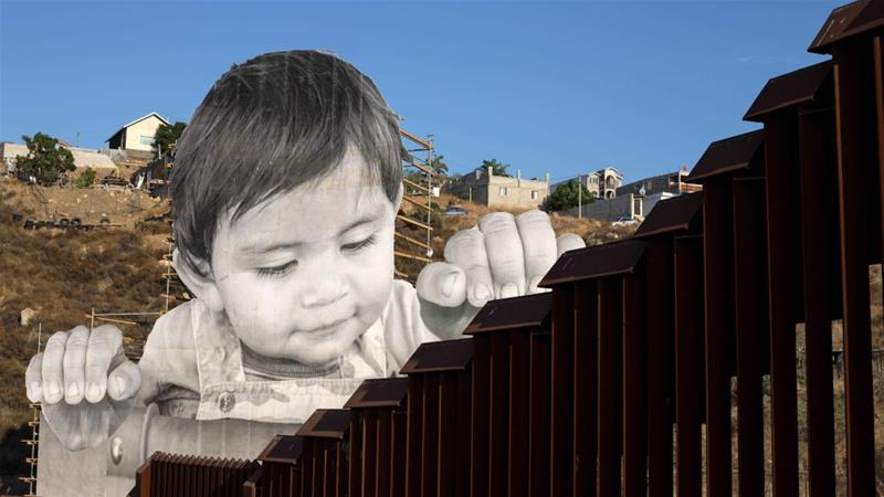 Giant portrait of toddler peers over US-Mexico border