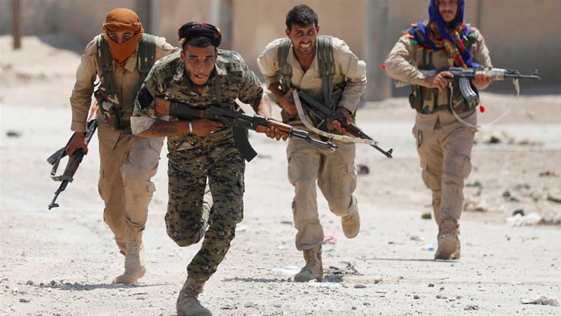 Kurdish fighters from the YPG run across a street in Syria's Raqqa while battling ISIL [Goran Tomasevic/Reuters]