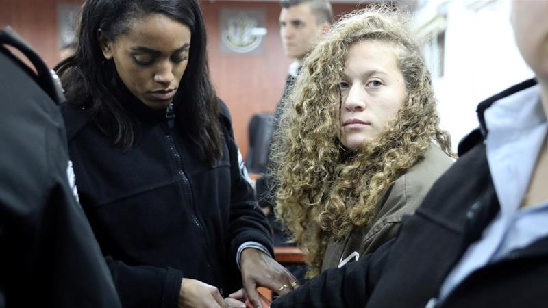 Palestinian teen Ahed Tamimi enters a military courtroom escorted by Israeli Prison Service personnel at Ofer Prison, near the West Bank city of Ramallah on January 1, 2018 [Ammar Awad/Reuters]