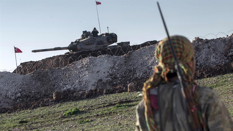 A Kurdish YPG fighter patrols near a Turkish tank in Esme village in Syria's Aleppo province in 2015 [File: Mursel Coban/Depo Photos via AP]