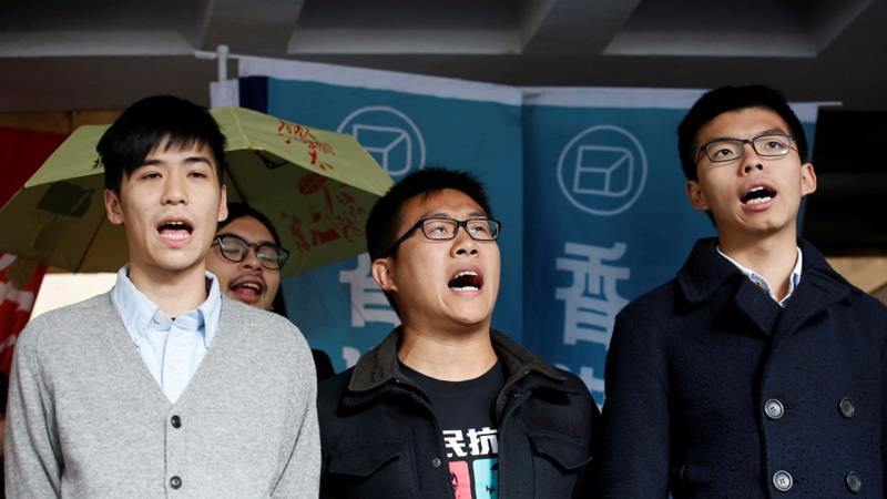 Raphael Wong, centre, and Joshua Wong, right, were jailed for contempt of court in Hong Kong on Wednesday [Bobby Yip/Reuters]