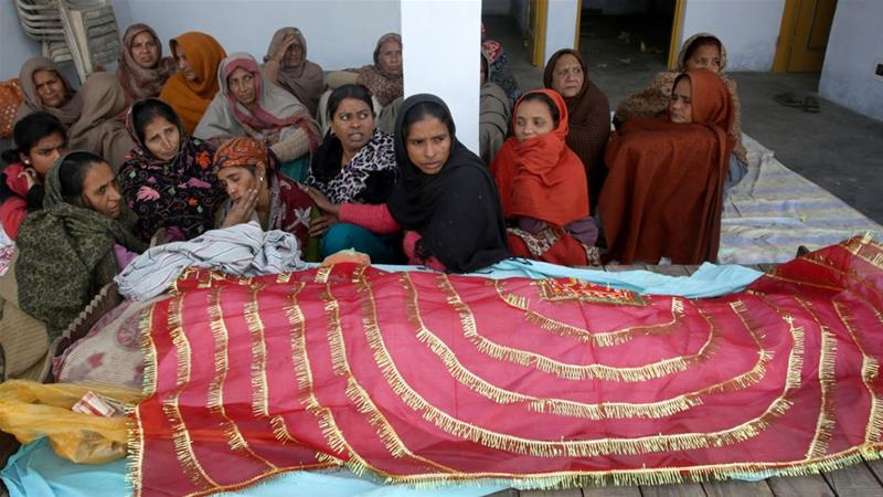 Relatives mourn over the dead body of Neelam Devi who was killed in the village of Pindi near Jammu [Jaipal Singh/EPA]