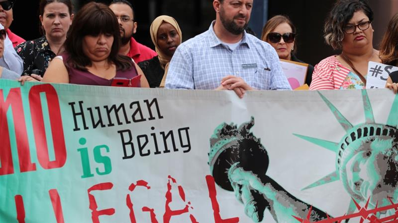 "People protest a pending deportation with a banner that reads ""no human being is illegal"", outside the federal building in San Diego, California, US [Mike Blake/Reuters]"