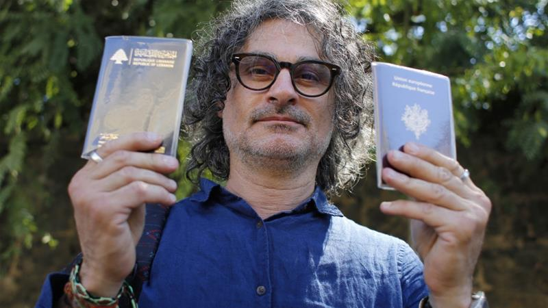 Lebanese film director Ziad Doueiri, holds up his Lebanese and French passports after being released by a military court, in Beirut on September 11, 2017 [File: AP Photo/Hassan Ammar]