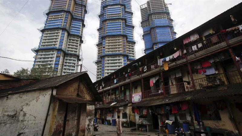 High-rise residential towers under construction are pictured behind an old residential building in central Mumbai [Vivek Prakash/Reuters]