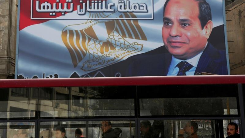 "People look out of a bus window in front of a huge banner for Egypt's President Sisi from the campaign titled ""So You Can Build It"", for the upcoming presidential election [Amr Abdallah Dalsh/Egypt]"