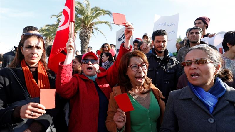 Protesters held up red cards at a rally against rising prices and tax increases [Zoubeir Souissi/Reuters]