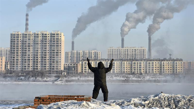 A man exercises in the morning as he faces chimneys emitting smoke behind buildings across the Songhua river in Jilin, Jilin province, China [Reuters]
