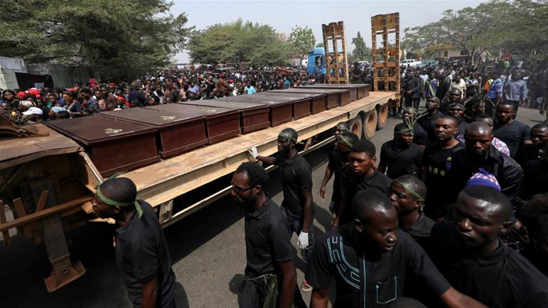 Men march along a truck carrying the coffins of people killed by the Fulani herdsmen, in Makurdi, Nigeria on January 11 [Afolabi Sotunde/Reuters]