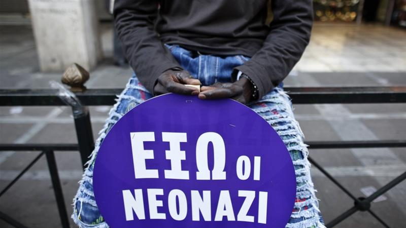 A migrant holds a sign decrying neo-Nazis in the Greek capital [Alkis Konstantinidis/Reuters]