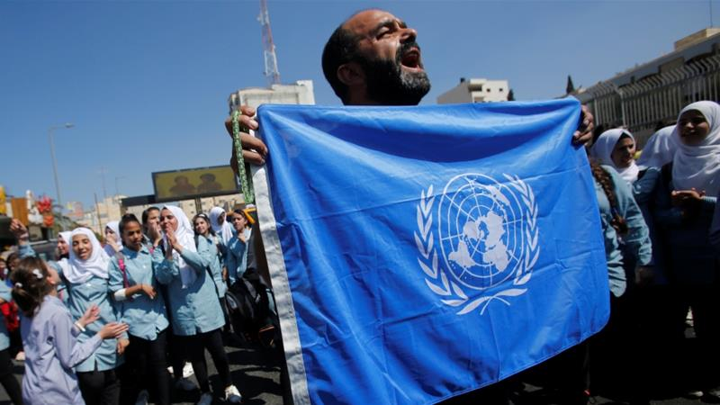 A Palestinian demonstrator holds a UN flag during a rally against a US decision to cut funding to UNRWA [File: Mussa Qawasma/Reuters]