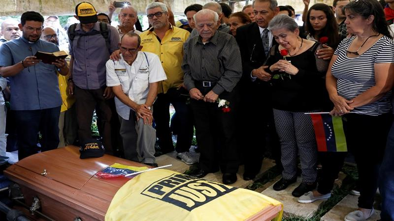 Relatives of opposition MP Fernando Alban during his burial in Caracas on Wednesday [Marco Bello/Reuters]