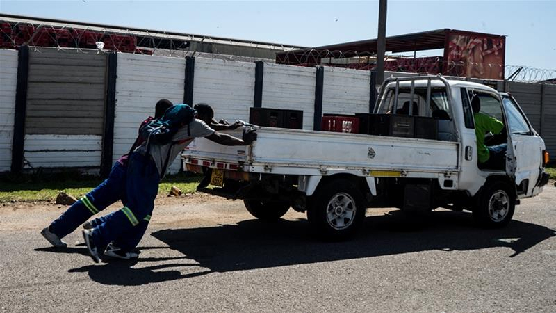 Men push their truck outside Delta Beverages in Bulawayo, opting to wait overnight in a queue although their car had run out of diesel [Tendai Marima/Al Jazeera]