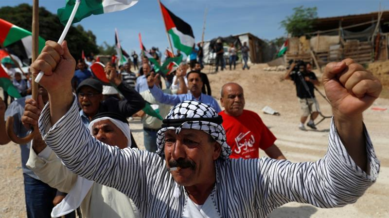 Demonstrators shout slogans during a protest against Israel's plan to demolish the Palestinian Bedouin village of Khan al-Ahmar, in the occupied West Bank, October 5, 2018 [Mohamad Torokman/Reuters]