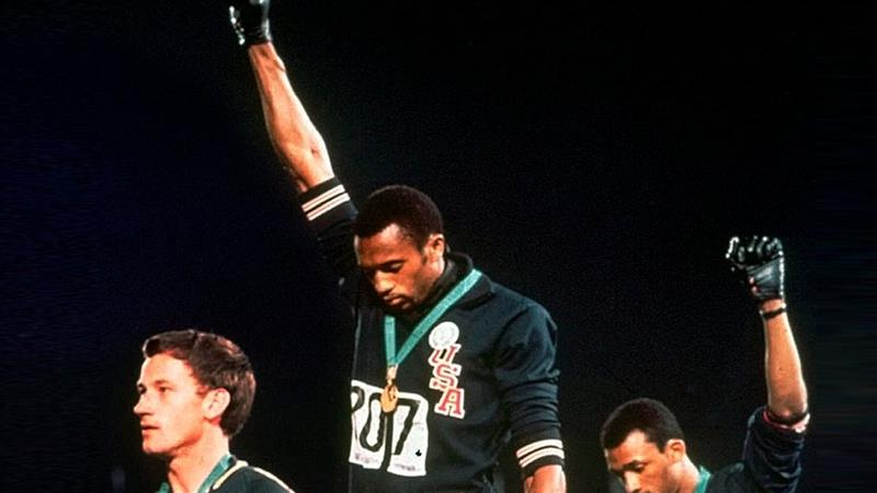 Australian silver medalist Peter Norman, left, stands on the podium as Americans Tommie Smith, centrr, and John Carlos raise their gloved fists in a human rights protest in 1968 [File: AP Photo]