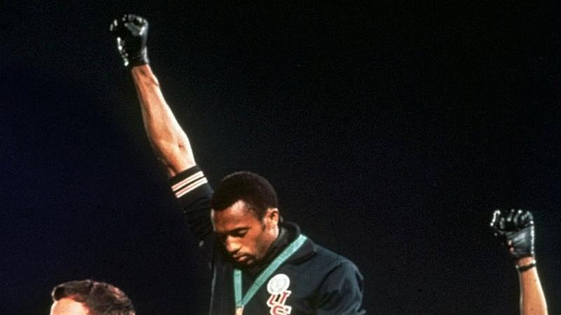 Australian silver medalist Peter Norman, left, stands on the podium as Americans Tommie Smith, center, and John Carlos raise their gloved fists in a human rights protest in 1968 [File: AP Photo]