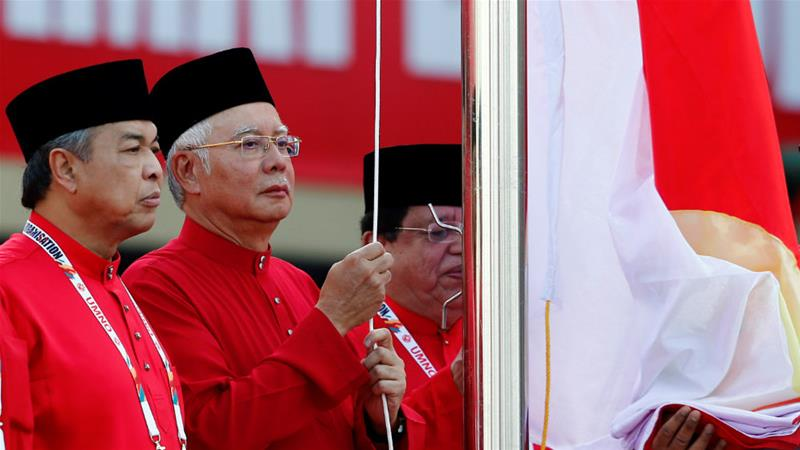 Ahmad Zahid Hamidi, left, raising the UMNO flag with former PM Najib in 2017 [File: Lai Seng Sin/Reuters]
