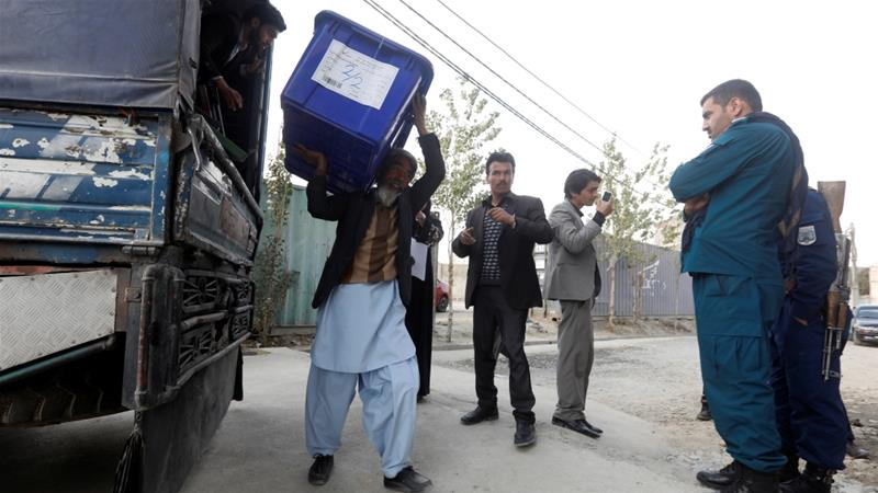 Election commission officials unload a ballot box with voting material outside a polling station in Kabul [Omar Sobhani/Reuters]