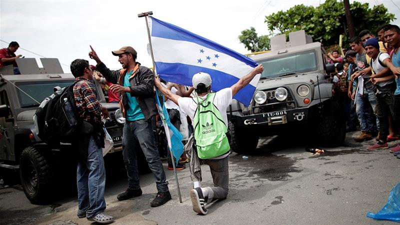 A Honduran migrant, part of a caravan trying to reach the US kneels holding a Honduras flag at a border checkpoint in Tecun Uman, Guatemala [Ueslei Marcelino/Reuters]