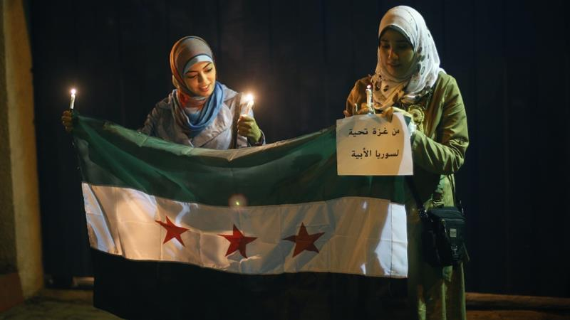 Palestinian women hold candles and a Syrian opposition flag during a protest against President Bashar al-Assad in front of the UN headquarters in Gaza City, August 23, 2013 [Suhaib Salem/Reuters]