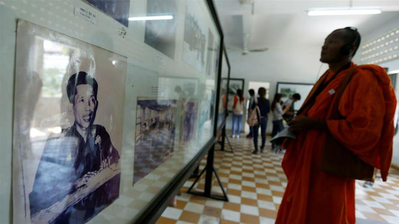 A Buddhist monk looks at a picture of Kaing Guek Eav, alias 'Duch', at Tuol Sleng Genocide Museum in Phnom Penh [File: Samrang Pring/Reuters]