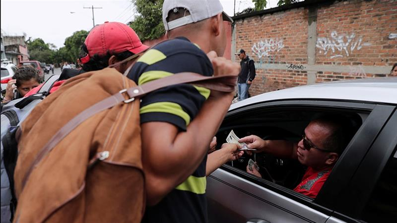 A motorist gives money to Honduran migrants outside a migrant shelter in Guatemala City [Luis Echeverria/Reuters]
