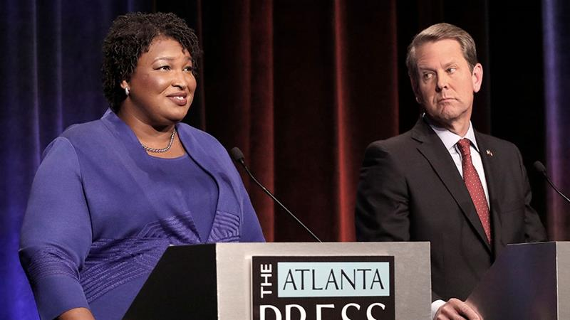 Democratic gubernatorial candidate for Georgia Stacey Abrams speaks as her Republican opponent Secretary of State Brian Kemp looks on during a debate in Atlanta, Georgia [John Bazemore/Reuters]