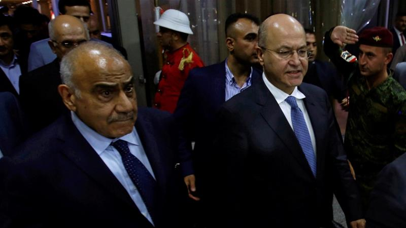 Barham Salih, Iraq's newly elected president, walks with Iraq's new Prime Minister Adel Abdul Mahdi at the parliament headquarters, in Baghdad, Iraq October 2, 2018 [Khalid al Mousily/Reuters]
